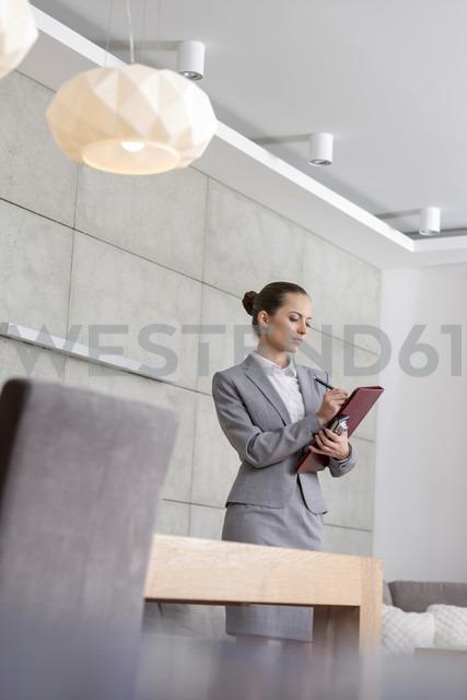 Businesswoman holding folder taking notes - LOF04568