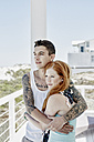 Happy young couple on a terrace of beach house looking to the sea - RORF00369