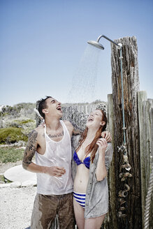 Young couple taking shower on the beach with clothes - RORF00378