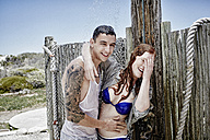 Young couple taking shower on the beach with clothes - RORF00381