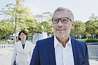 Confident businessman outdoors with woman in background - RORF00385