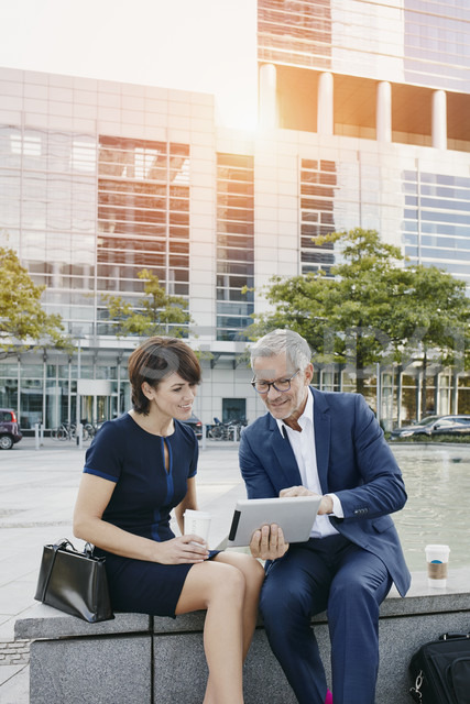 Businessman and businesswoman with digital tablet outdoors - RORF00391