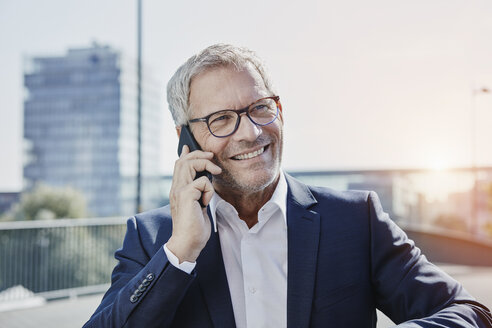 Smiling businessman on cell phone outdoors - RORF00400