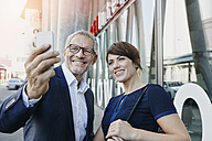 Businessman and businesswoman taking a selfie outdoors - RORF00409