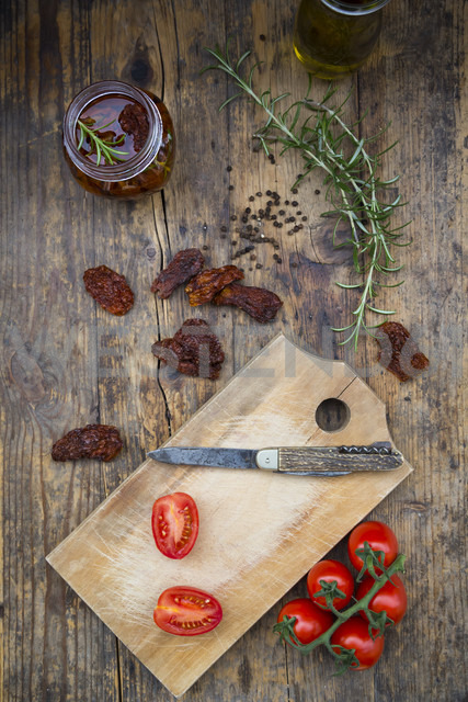 Glass of pickled dried tomatoes and ingredients on wood - LVF05531