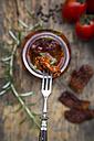 Pickled dried tomato skewered on fork, close-up - LVF05537
