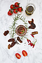 Glass of pickled dried tomatoes and ingredients on white marble - LVF05540