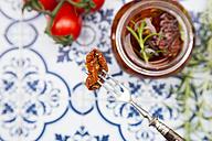 Pickled dried tomato skewered on fork, close-up - LVF05543