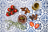 Glass of pickled dried tomatoes and ingredients on tiles - LVF05546