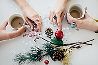 Hands of two women holding cups of coffee on a tabletop with Christmas decoration - LCUF00075