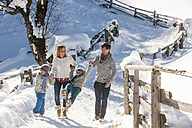 Happy family walking in snow - HHF05458