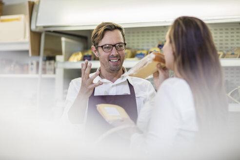 Portrait of grocer serving customer in a farm shop - ZEF11275
