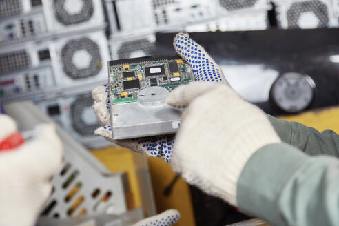 Worker holding hard disk in computer recycling plant - RKNF00400
