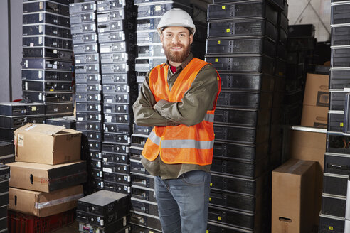 Worker in computer recycling plant, portrait - RKNF00415
