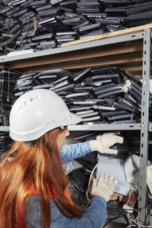 Female worker in computer recycling sorting shelf - RKNF00445