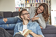 Happy couple relaxing together in the living room - FMKF03137