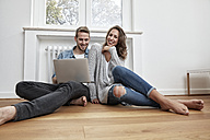 Smiling couple sitting on the floor  with laptop - FMKF03140
