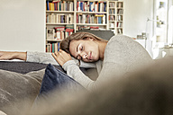 Young woman relaxing with eyes closed on couch in the living room - FMKF03143