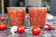 Two glasses of homemade tomato sauce and ingredients on stone - SARF03040
