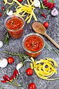 Glasses of homemade tomato sauce, ingredients and pasta on stone - SARF03043