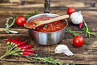Saucepan of homemade tomato sauce and ingredients on wood - SARF03046