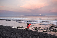 Spain, Tenerife, boy carrying surfboard on the beach at sunset - SIPF01005