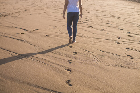 Young woman walking in sand on the beach - SIPF01015