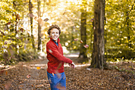 Smiling boy throwing leaves in the air in the autumnal forest - DIGF01397