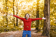 Smiling boy throwing leaves in the air in the autumnal forest - DIGF01400