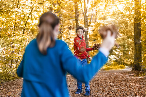 Mother and son playfighting with leaves in the autumnal forest - DIGF01403