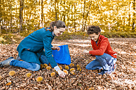 Mother and son collecting sweet chestnuts in the autumnal forest - DIGF01412