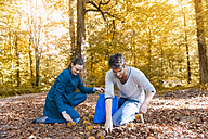 Couple collecting sweet chestnuts in the autumnal forest - DIGF01418