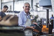 Smiling shoemaker working on shoe in workshop - ZEF11330