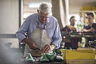 Shoemaker working on shoe in workshop - ZEF11339