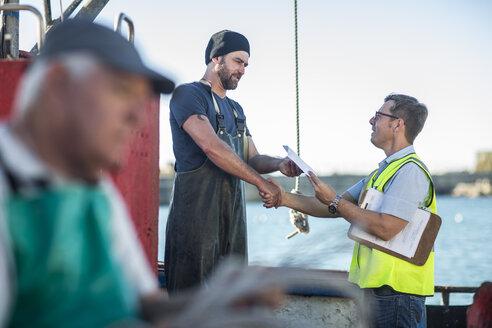 Fisherman on trawler talking to inspector - ZEF11411