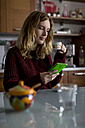 Woman with cup of coffee sitting in the kitchen looking at smartphone - MAUF00853