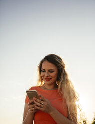 Smiling blond woman looking at smartphone in front of sky - AIF00416