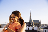 Austria, Vienna, two happy friends embracing on roof terrace with stephansdom in the background - AIF00425