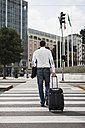 Back view of businessman with suitcase crossing the street - MAUF00880
