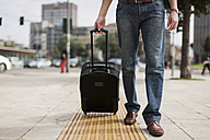 Legs of businessman with suitcase on pavement - MAUF00883