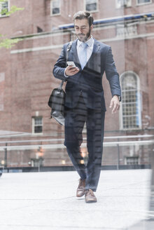 USA, New York City, businessman walking in Manhattan looking at cell phone - UUF08934