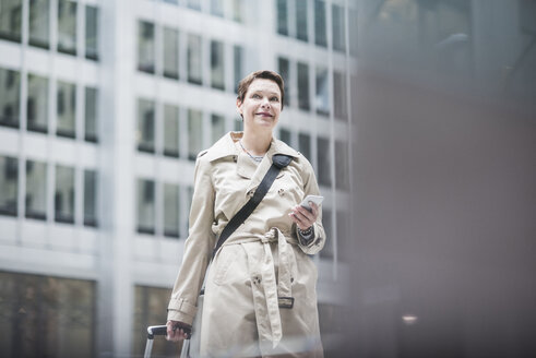 USA, New York City, smiling woman in Manhattan with cell phone - UUF08943