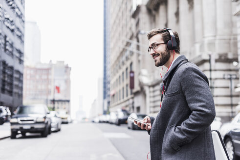 USA, New York City, smiling businessman with cell phone and headphones on the go - UUF08964