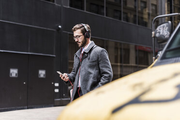 USA, New York City, businessman with cell phone and headphones on the go - UUF08967
