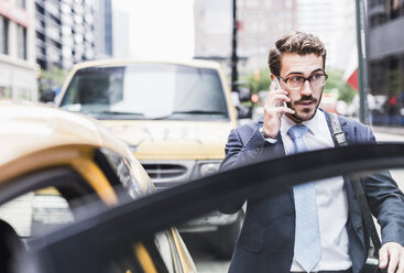 USA, New York City, businessman in Manhattan on cell phone entering a taxi - UUF08970