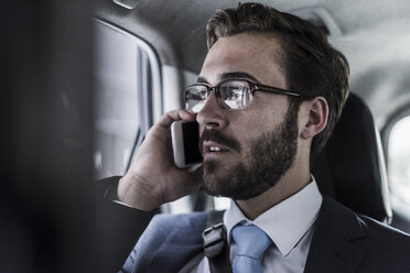 Businessman on cell phone in a car - UUF08973