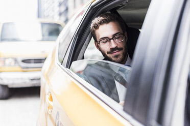 USA, New York City, smiling businessman in a taxi - UUF08976