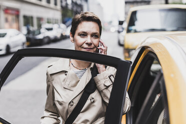 USA, New York City, woman in Manhattan on cell phone entering a taxi - UUF08982