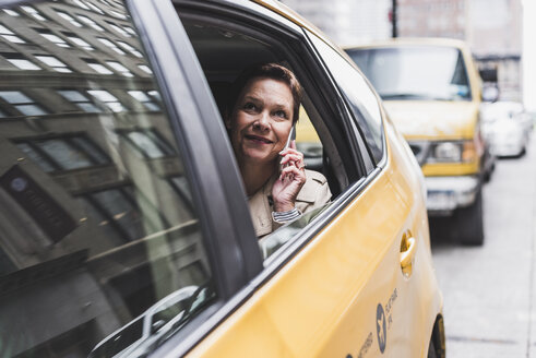 USA, New York City, smiling woman in taxi on cell phone - UUF08985