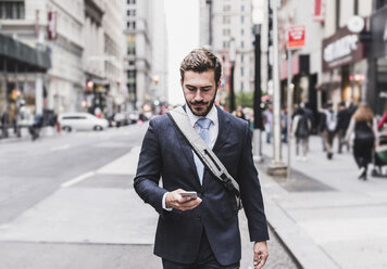 USA, New York City, businessman walking in Manhattan looking at cell phone - UUF08991